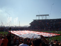 Streamers fly in the air as people cheer with Large USA Flag hel Stock Image