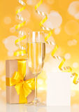 Streamers, gift box, card and champagne glass Stock Photos