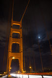 Streaming cars on Golden Gate Bridge, San Francisco, California. Vertical shot of cars lights streaming under span of Golden Gate Bridge at night in San Stock Photo