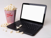 Streaming Movies Concept. A laptop and popcorn, streaming movies over the Internet, blank screen for copy Stock Photos