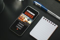 Tv series website app in a mobile phone screen, placed on a black desk. Streaming series app template design in a mobile phone screen placed on a desk to watch stock image