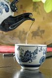 Streaming tea into cup. Hot prepared tea pouring steaming tea from antique oriental teapot into a white china cup on table with wood carrying tray having horses Stock Photos