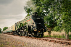 Streamlined Steam Train. A steam train passes, approaching Wymondham Abbey station in Norfolk, it is hauled by 60009 A4 Pacific Sir Nigel Gresley painted in BR Royalty Free Stock Images