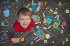 Streat portrait of the preschool boy playing cars in the chalk drawn city