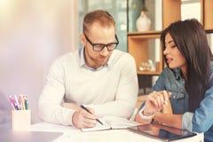 Strebend Kollegen, die bei Tisch zusammenarbeiten Lizenzfreies Stockfoto