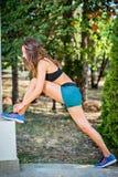 streching和做锻炼的活跃少妇在公园 适合的f 免版税库存图片