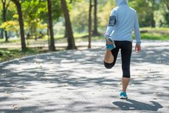 streching在公园的年轻运动员妇女室外,母赛跑者使准备好兴奋跑步在路外面,亚洲健身步行 免版税库存图片