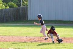 Streck för barnserien i basebollsoftballspelare för tredje basen, medan den andra basemanen når för boll fotografering för bildbyråer