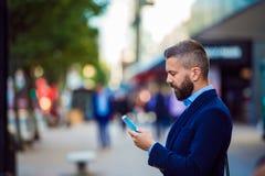拿着智能手机的行家经理,发短信外面在stree 库存照片
