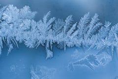 Streep van de winter ijzig wit ijzig patroon op blauwe glasruit stock afbeeldingen