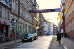 In the street in  Aarhus city at dusk. Beautiful sight in Aarhus,Denmark in the street at dusk,someone is riding a bike,buildings on both sides Royalty Free Stock Image