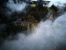 Street from above trough a misty forest at autumn, aerial view flying through the clouds with fog and trees Royalty Free Stock Photos
