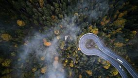 Street from above trough a misty forest at autumn, aerial view flying through the clouds with fog and trees Royalty Free Stock Photography