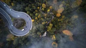 Street from above trough a misty forest at autumn, aerial view flying through the clouds with fog and trees Royalty Free Stock Photo
