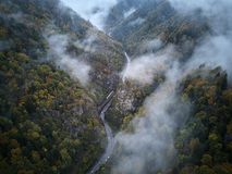 Street from above trough a misty forest at autumn, aerial view flying through the clouds with fog and trees Stock Images