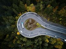 Street from above trough a misty forest at autumn, aerial view flying through the clouds with fog and trees Stock Photography