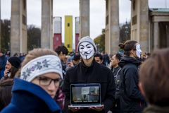 Street action of Berlin Vegans `Cube of Truth`. BERLIN - NOVEMBER 12, 2017: Street action of Berlin Vegans `Cube of Truth` in the Anonymous mask near Brandenburg Royalty Free Stock Photo