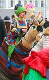 Street actor in funny carnival costume rides a horse puppet Stock Photography