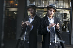 Street actor magician in a hat and a strict suit is leaning against a mirror display. Royalty Free Stock Photos