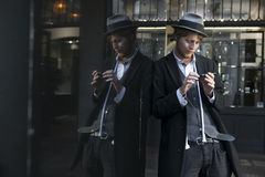 Street actor magician in a hat and a strict suit is leaning against a mirror display. Royalty Free Stock Images