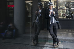 Street actor magician in a hat and a strict suit is leaning against a mirror display. Stock Images