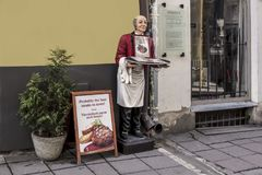 Street advertisement. Doll-waiter on the narrow street of old Tallinn. Intended to call holiday-makers to taste the Estonian kitchen Stock Photography