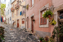 Street of the Alfama district, Lisbon. Typical narrow street and cobblestone floor of Alfama district in Lisbon, capital of Portugal Royalty Free Stock Images