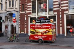 AMSTERDAM, NETHERLANDS - JUNE 25, 2017: Street eatery with fast food in the center of Amsterdam on Damrak street in morning. On the street also there are Royalty Free Stock Photography
