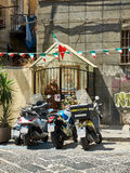 Street altar in honor of Padre Pio in Naples. Campania, Italy. Naples, Italy - August 7, 2017. Scooters parked in front of a street altar in honor of Padre Pio Stock Photos