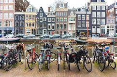 Street in Amsterdam, yachts on the canal and bicycle parking in the foreground stock images