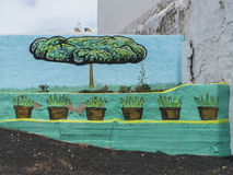 Street Art –tree and flowerpots in the grey. Street Art on the Canary Islands. Painting of green tree and flowerpots bringing a grey wall to life royalty free stock image