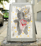 Street art bunny with a red dripping heart on the base of a sidewalk lamppost. Street art wheat paste design of a grey stuffed bunny with a red dripping heart Royalty Free Stock Photo