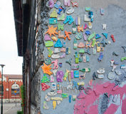Street art composition with the amusing figures of mobile phones, people, and other symbols of life on the wall Stock Photos
