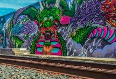 Street Art Dragon. Street Art of Sacramento displaying dragon along rail line Royalty Free Stock Images