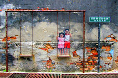 Street Art in Georgetown. Penang, Malaysia. Street Art in Penang Malaysia. Brother and sister on a swing Royalty Free Stock Image