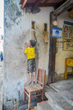 Street art graffiti of boy standing on a chair in George Town city centre, Malaysia. Interesting street art graffiti of boy standing on a chair in George Town Royalty Free Stock Images