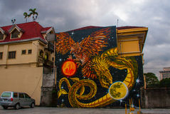 Street art graffiti. The picture of the dragon and the eagle with the planets. Manila Philippines Stock Photo