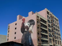 Street art in Los Angeles Fashion District. Image of a woman in a long dark skirt (or pinafore) and white blouse holding a cockerel, painted on an  apartment Royalty Free Stock Photo