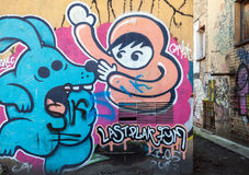 Street art, old wall with grungy cartoon graffiti Stock Photography