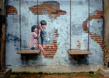 STREET ART Painting on the the wall two cute little sisters havi Royalty Free Stock Image