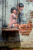 STREET ART Painting on the the wall two cute little sisters havi Stock Photography