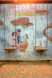 STREET ART Painting on the the wall two cute little sisters havi Stock Image