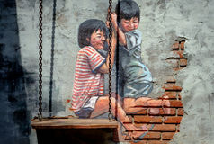 STREET ART Painting on the the wall two cute little sisters havi Stock Images