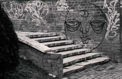 Street art. Street photography: graffiti on a brick wall and stairs on black and white Royalty Free Stock Photography
