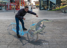 Street art showing optical illusion. ALMERE, NETHERLANDS - 27 OCT. 2015: Man showing the power of 3D optical illusion on a street painting of a bicycle in the Royalty Free Stock Photo