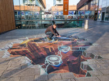 Street art showing optical illusion. ALMERE, NETHERLANDS - 27 OCT. 2015: Man showing the power of 3D optical illusion on a street painting of a crater in the Stock Image