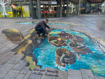Street art showing optical illusion. ALMERE, NETHERLANDS - 27 OCT. 2015: Man showing the power of 3D optical illusion on a street painting of men in wooden tubs Royalty Free Stock Images
