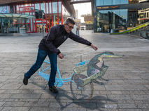 Street art showing optical illusion. ALMERE, NETHERLANDS - 27 OCT. 2015: Unknown man shows the power of 3D optical illusion of a street painting by an unknown royalty free stock photo