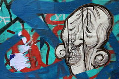 Street art - ugly face. Ugly face painted  on wall with many colors Stock Images