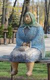 Street art in the Ukrainian capital Kyiv. Sculpture of an old woman sitting on the bench is situated in the park royalty free stock images